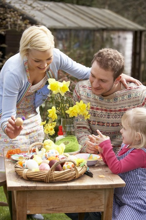 familia en jardin: Familia decorar huevos de Pascua en la tabla al aire libre Foto de archivo