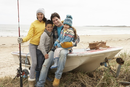 Family Group Sitting On Boat With Fishing Rod On Winter Beach photo