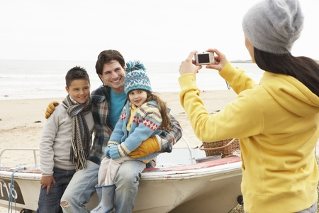 Mother Taking Family Photograph On Winter Beach photo