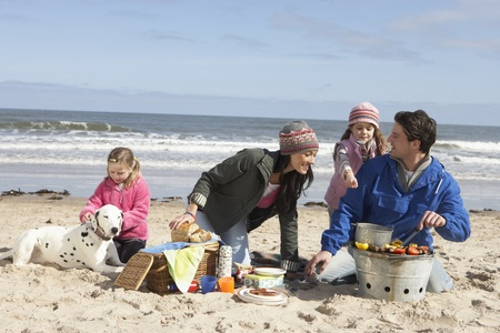 Family Having Barbeque On Winter Beach photo