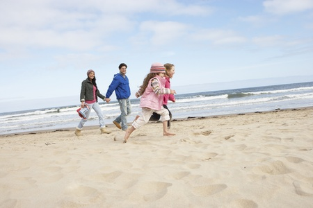 Family Walking Along Winter Beach photo
