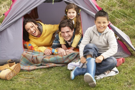 camping tent: Young Family Relaxing Inside Tent On Camping Holiday