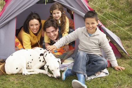 holiday pets: Young Family With Dog Relaxing Inside Tent On Camping Holiday