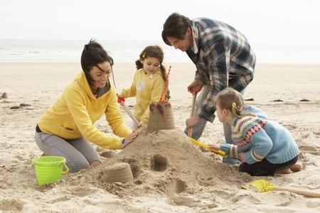 sandcastle: Family Building Sandcastle On Winter Beach
