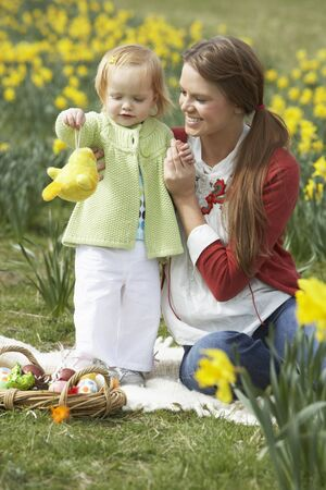 two year old: Mother And Daughter In Daffodil Field With Decorated Easter Eggs Stock Photo