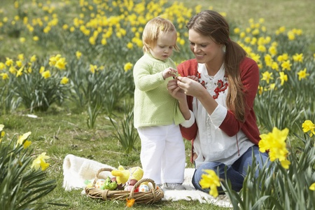 Mother And Daughter In Daffodil Field With Decorated Easter Eggs Stock Photo