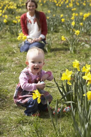 easter egg hunt: Mother And Daughter In Daffodil Field With Decorated Easter Eggs Stock Photo