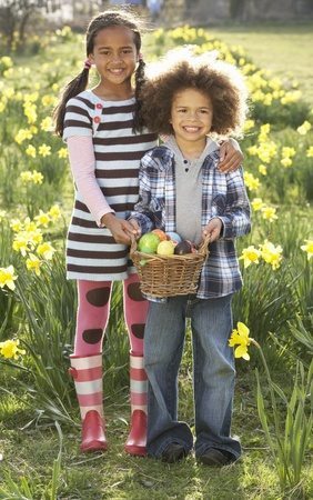 Brother And Sister Having Easter Egg Hunt In Daffodil Field photo