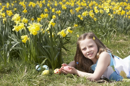 seven persons: Girl On Easter Egg Hunt In Daffodil Field Stock Photo