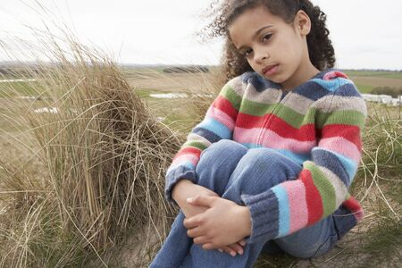 Young Girl Sitting Amongst Dunes On Winter Beach photo