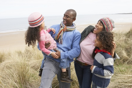 Family Walking Along Dunes On Winter Beach photo