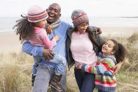 family walking: Family Walking Along Dunes On Winter Beach