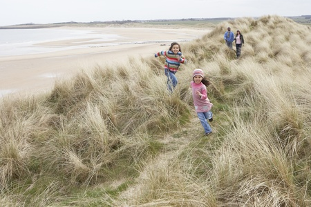 Family Walking Along Dunes On Winter Beach photo