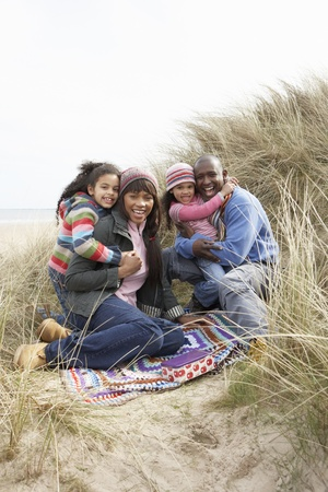 Family Sitting On Blanket In Dunes On Winter Beach photo