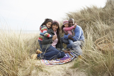 Family Sitting In Dunes Enjoying Picnic On Winter Beach photo