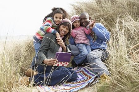 Family Sitting In Dunes Enjoying Picnic On Winter Beach photo
