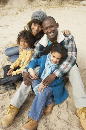 Family Sitting On Winter Beach photo
