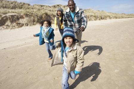 Family Running On Winter Beach Stock Photo - 10199167