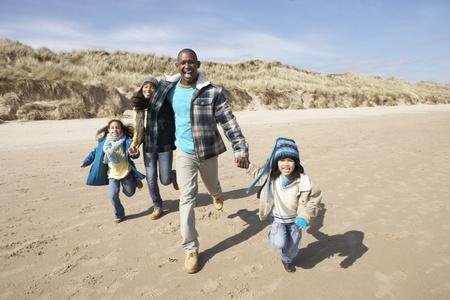 Family Running On Winter Beach photo