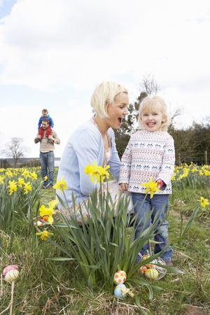 Family On Easter Egg Hunt In Daffodil Field photo