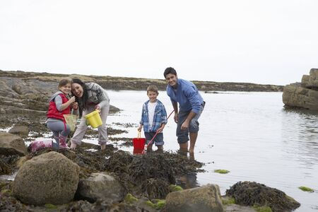 Young family at beach collecting shells Stock Photo