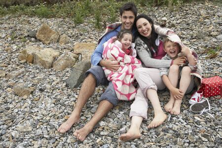 Family on beach with blankets photo
