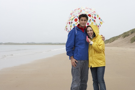 Young couple on beach with umbrella photo