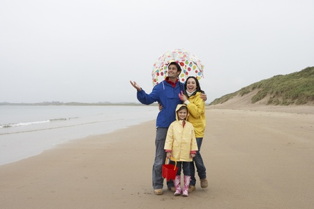 5 year old girl: Happy family on beach with umbrella