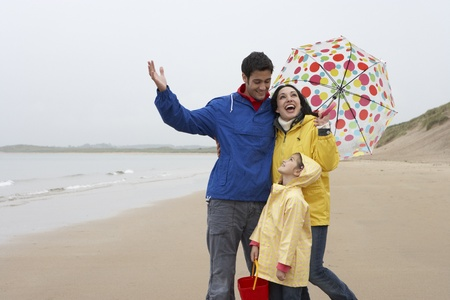 Happy family on beach with umbrella photo