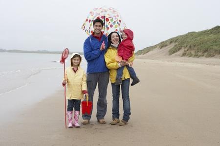 raincoat: Happy family on beach with umbrella