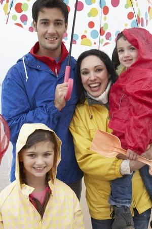 Happy family on beach with umbrella photo