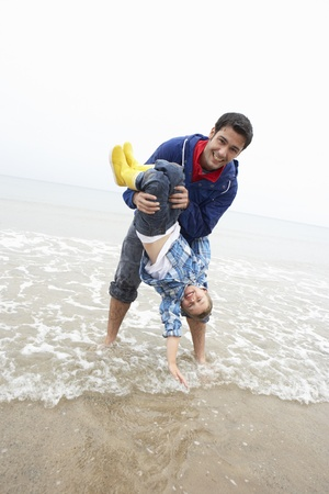 upside down: Happy father with son on beach