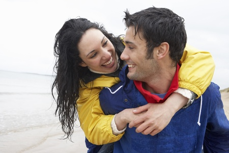 at each other: Happy couple on beach in love Stock Photo