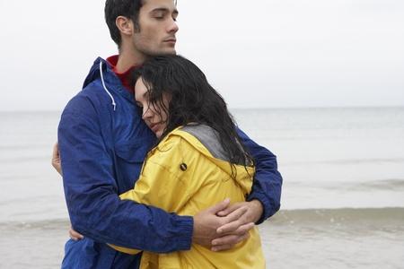 raincoat: Couple on beach in love