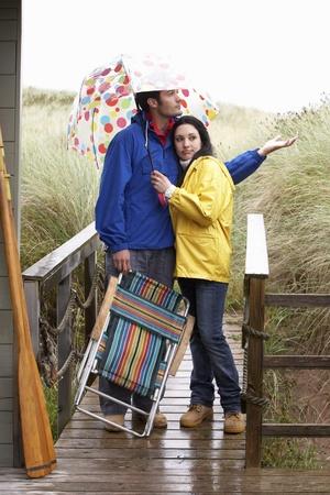 sotto la pioggia: Giovane coppia sulla spiaggia con ombrellone Archivio Fotografico