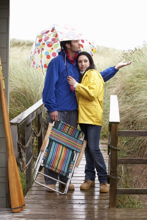 couple in rain: Young couple on beach with umbrella Stock Photo