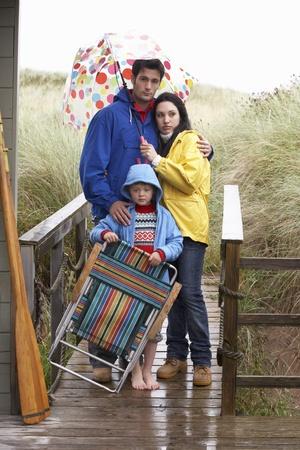 Family on beach with umbrella photo