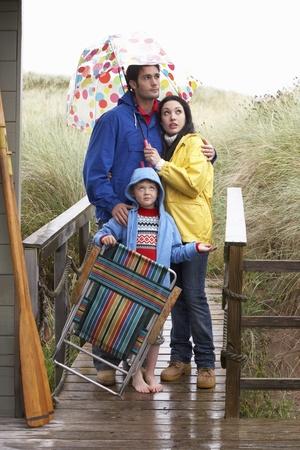uomo sotto la pioggia: Famiglia sulla spiaggia con ombrellone