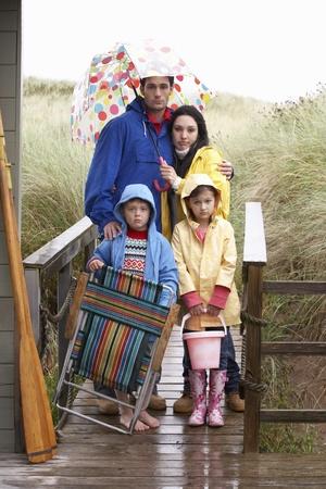 mujer decepcionada: Familia de playa con paraguas Foto de archivo