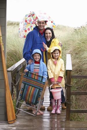 precipitacion: Familia de playa con paraguas Foto de archivo