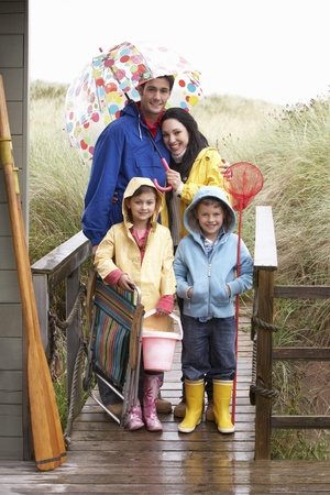 Family on beach with umbrella photo