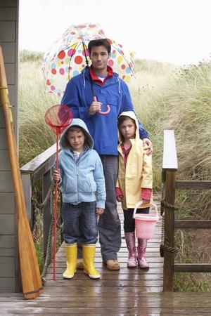 sotto la pioggia: Padre con i bambini sulla spiaggia