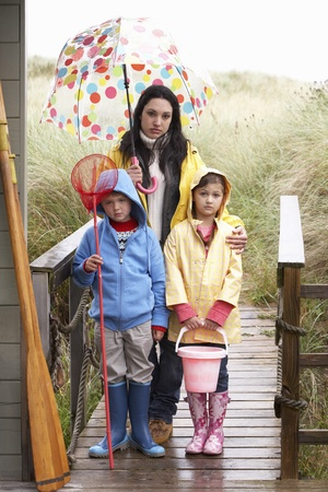 rubber boots: Sad mother and children on beach Stock Photo