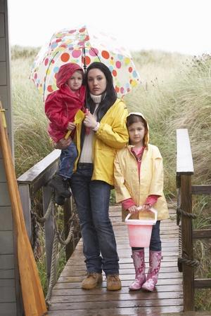 Sad mother and children on beach photo