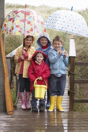 raincoat: Children posing with umbrella Stock Photo