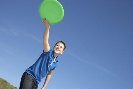 Boy playing frisbee on beach photo