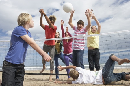 Teenagers playing volleyball photo