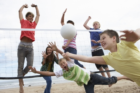 Teenagers playing volleyball Stock Photo