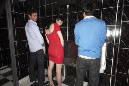 Woman and two men standing at mens urinal
