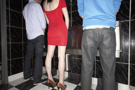 odd: Woman and two men standing at mens urinal